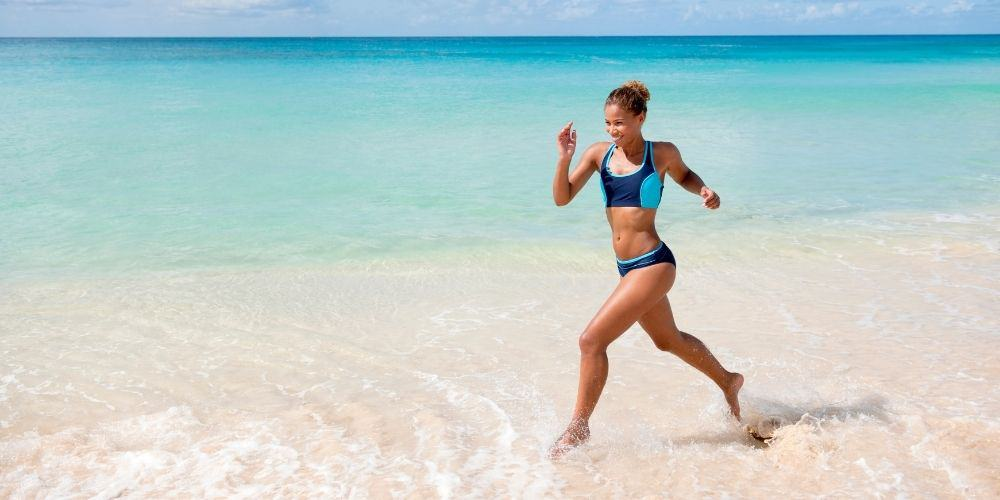 woman running barefoot on the beach